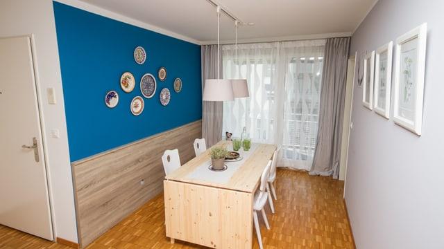 In der einen Ecke besitzen Daniel und Andrea neu einen ausziehbaren Esstisch. Mit der blauen Wand wirkt die Ecke frisch und einladend.