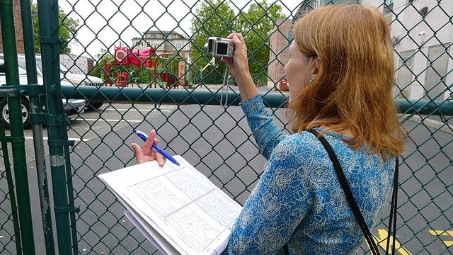Eine Frau fotografiert hinter einem Zaun.