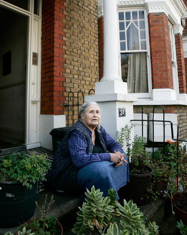 Doris Lessing sitzt vor ihrem Haus auf der Treppe.