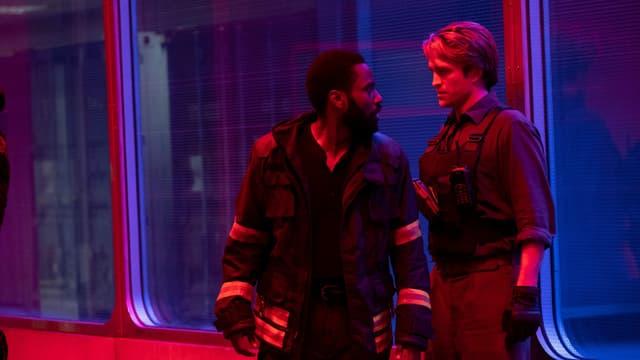 Szene: Der Protagonist (Washington) und Neil (Pattinson) unterhalten sich vor einer Scheibe.