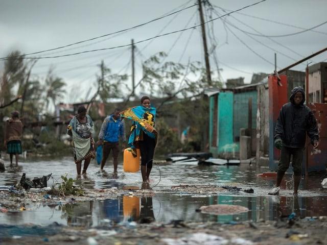 Menschen in überschwemmter Strasse.