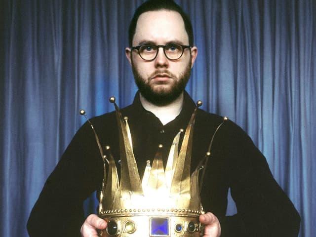 Mann trägt Krone in den Händen