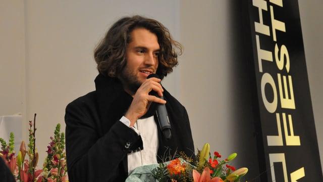 Ein Mann, ins Mikrofon sprechend, Blumen in der Hand.