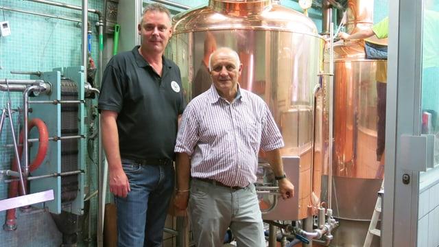 Zwei Braumeister in der Brauerei vor einem Braukessel.