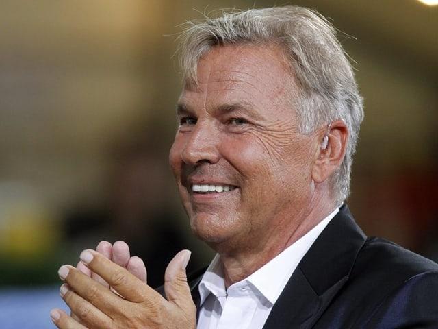 Fernsehmoderator Kurt Zurfluh lächelt und klatscht die Hände zusammen.