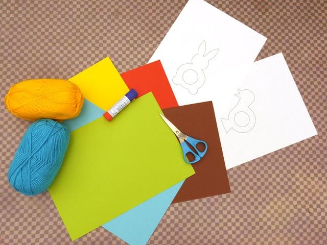 Auf diesem Bild sehen Sie die Vorlage zum Ausdrucken, eine Schere, einen Leimstift, farbige Wolle und dickes farbiges Papier.