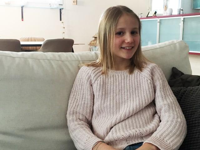 Ein Mädchen sitzt auf dem Sofa und lacht