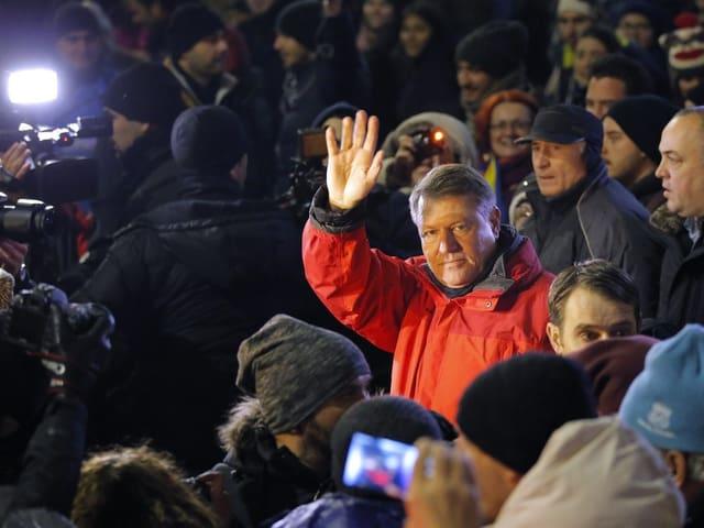 Klaus Iohannis an einer Demonstration in Bukarest. Seine rote Jacke hebt ihn von den anderen Demonstranten ab.