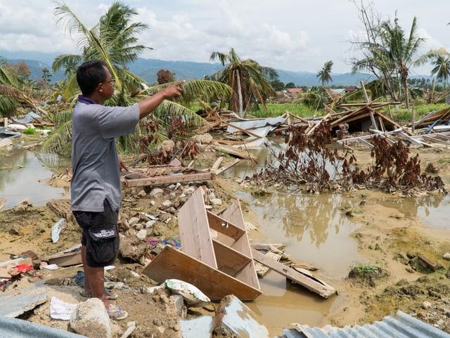 Mann zwischen Trümmerteilen stehend und nach rechts zeigend