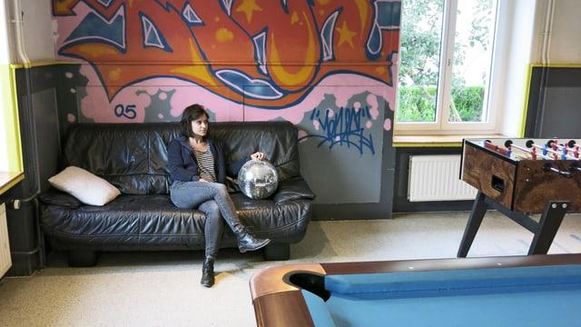 Eine Frau sitzt auf dem Sofa zwischen Töggelikasten und Billardtisch