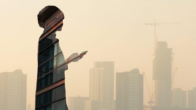 Die Silhouette einer Frau mit einem Handy in der Stand ist vor einer Skyline zu sehen.