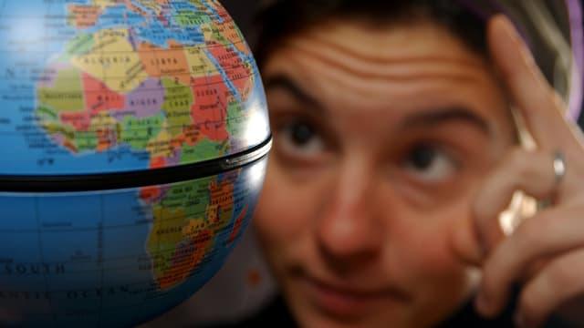 Eine Frau schaut sich einen Globus an.
