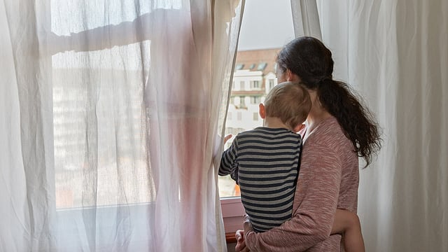 Eine Frau steht mit ihren zwei Kindern am Fenster.