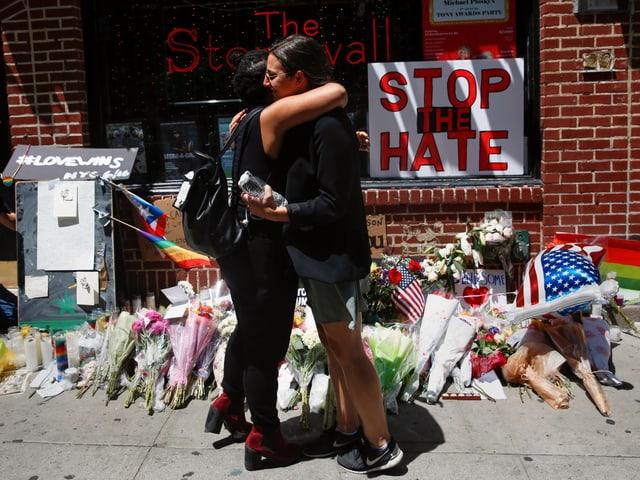 """Zwei Frauen umarmen sich vor der Bar """"The Stonewall Inn"""". Am Boden vor der Bar liegen viele Rosensträusse. An der Wand ein Schild """"Stop the Hate""""."""