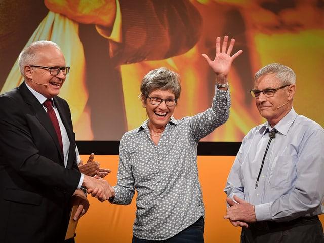 Zwei Männer und eine Frau auf einer Bühne.