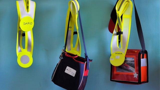 Kindergartentaschen und Kindergartendreiecke hängen an Garderobenhaken.