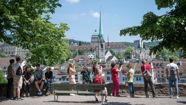 Touristen fotografieren auf dem Lindenhof die Zürcher Innenstadt.