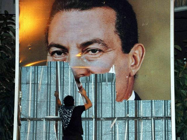 Ein Ägyptischer Demonstrant reist ein Poster des ehemaligen Präsidenten Hosni Mubarak herunter.