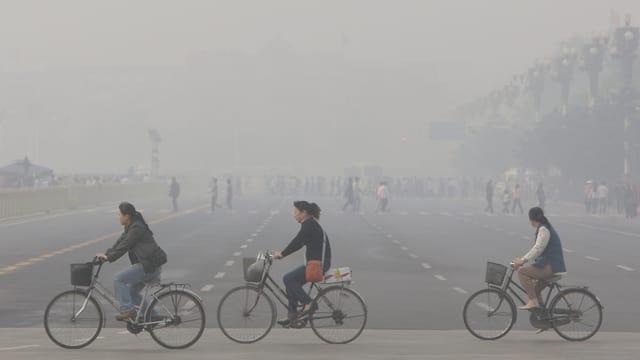 Velocipedistas cumbattan cun il smog a Peking.