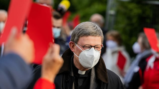 Kardinal Rainer Maria Woelki, Erzbischof von Köln, geht durch einen Spalier aus Gemeindemitgliedern, die ihm vor der Kirche St. Maria vom Frieden die Rote Karte zeigen.