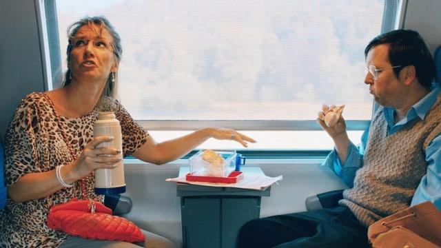 Eine Frau und ein Mann sitzen in einem Zugabteil. Die Frau hält eine Thermoskanne in der Hand und der Mann isst ein Brötchen.