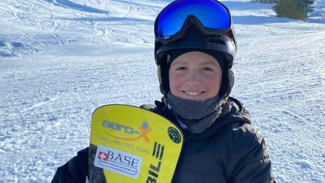 Gaël hält sein Snowboard in der Hand, steht auf der Piste und grinst in die Kamera