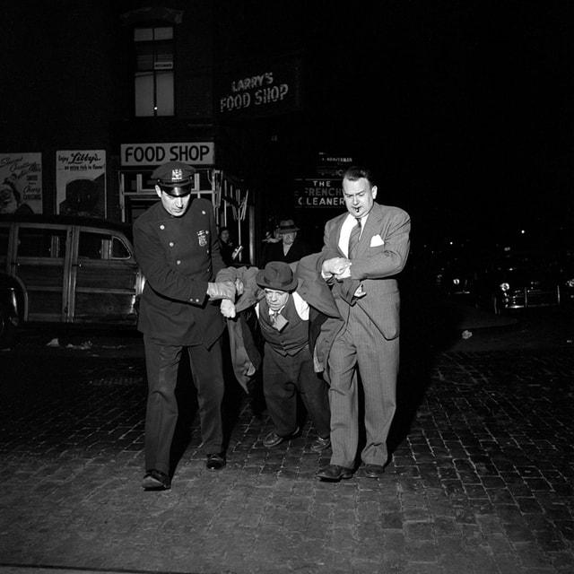 schwarz weiss Fotografie. zwei polizisten transportieren einen Betrunkenen Mann ab.