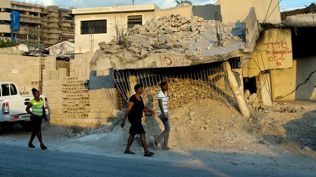 Mehrere Haitianer gehen an einem zerstlörten Haus vorbei