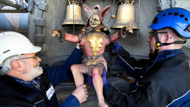 Zwei Arbeiter mit Helm nehmen die Figur ab der berühmten Turm-Uhr.