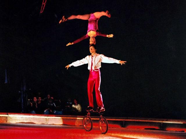 Adrian Steiner steht auf einem Fahrrad und balanciert eine Frau Kopf an Kopf