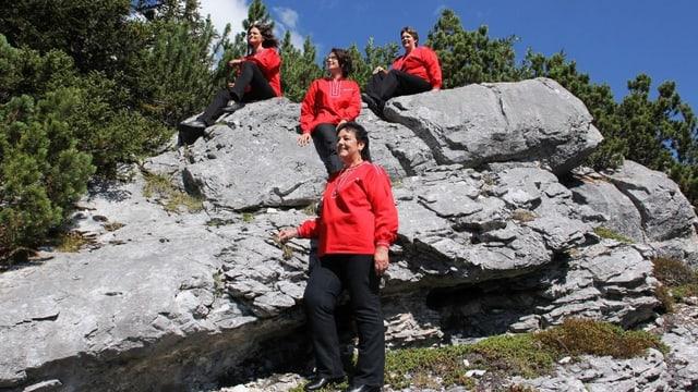 Die Sängerinnen tragen alle rote Blusen und sitzen auf einem grossen Stein inmitten der Bergwelt.