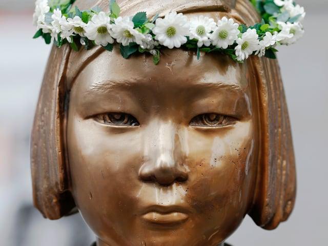 Kopf einer Bronzestatue eines asiatischen Mädchens, jemand hat einen Kranz aus weissen Büten auf den Kopf gelegt.