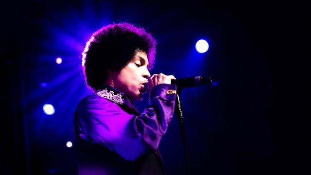 Ein Mann mit Afrolocken im violetten Scheinwerferlicht.