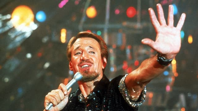 Ein Mann im Rampenlicht mit Mikrofon.