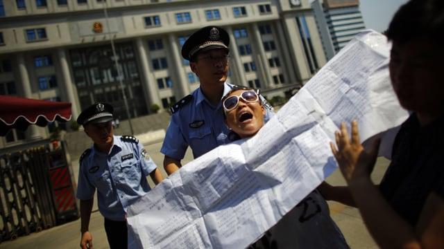 Die Polizei führt eine Demonstrantin ab.