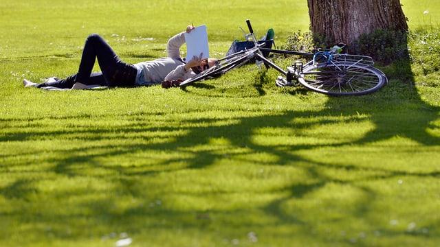 Ein Mann liegt neben seinem Velo im park am Zürisee auf der Wiese und liest Zeitung. (keystone)