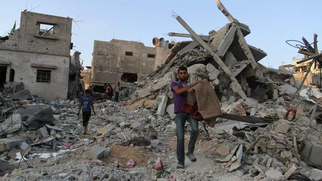 Palästinenser tragen ihre Habe aus den Trümmern eines Hauses in Beit Hanun.