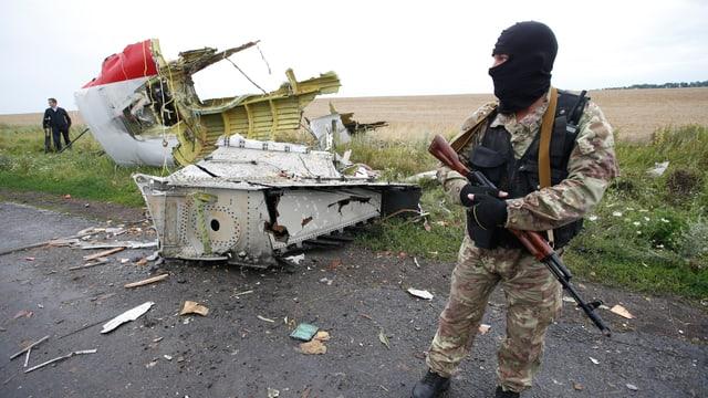 Ein pro-russischer Kämpfer steht vor einem Wrackteil