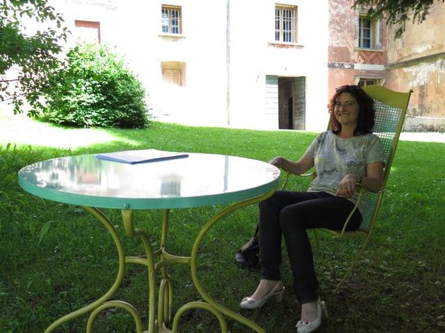 Anna Giacometti sitzt in einem grossen Gartenstuhl im Garten des Palazzo im Schatten.