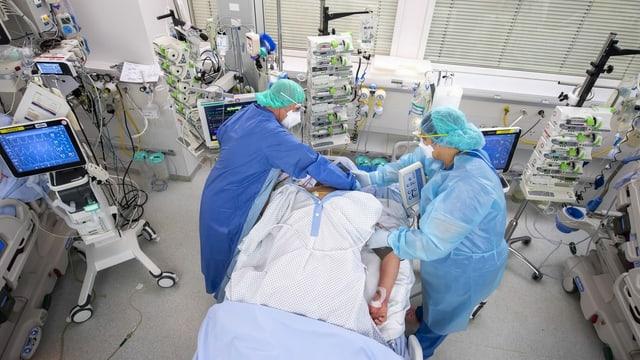 Dus tgirunzs u tgirunzas en vestgids da protecziun che tgiran in pazient sin la staziun intensiva.
