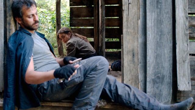 Ein Mann in einem Fenster, hinter ihr eine junge Frau.