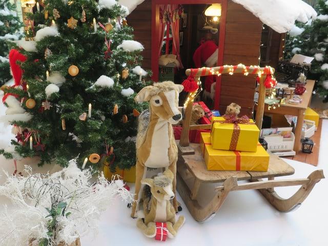 Weihnachtsdekoration mit Rehen, einem Schlitten und Häuschen