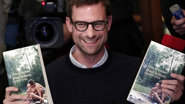 Ein Mann mit markanter Brille hält strahlend zwei Bücher in die Kamera.