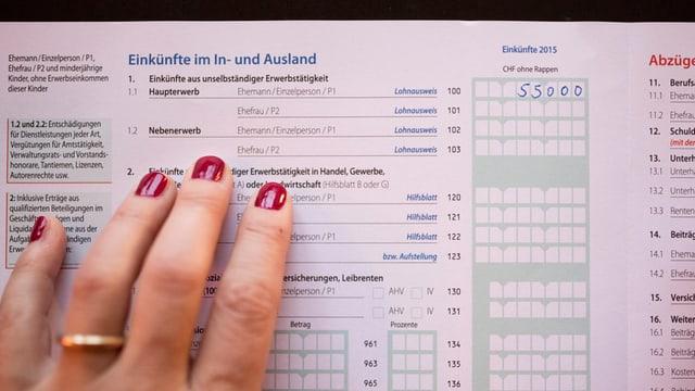 Eine Hand, welche eine Steuererklärung ausfüllt.