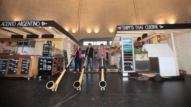 Drei Alphornisten zwischen zwei Marktständen in der Markthalle Basel.