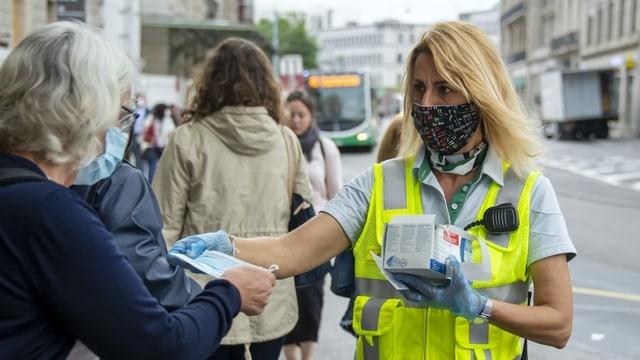 Eine Mitarbeiterin der Basler Verkehrs-Betriebe verteilt Schutzmasken am Bahnhof SBB in Basel.