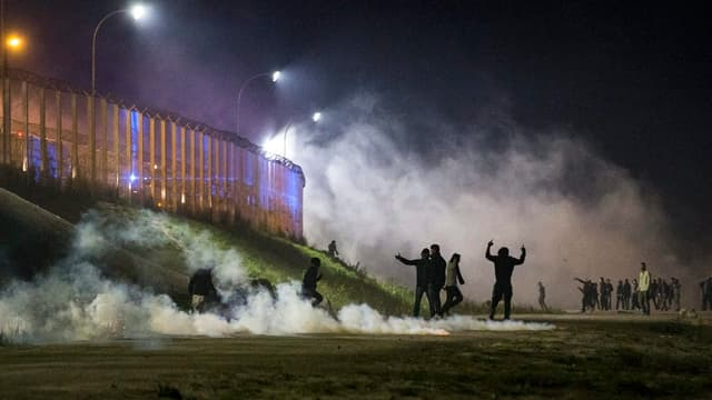 Migrants fruntan cun la polizia franzosa cura che questa attatgan la saiv dal champ da fugitivs numnà «tschungla» a Calais.