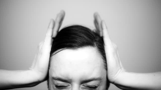 Eine Frau hält sich beide Hände an die Schläfen