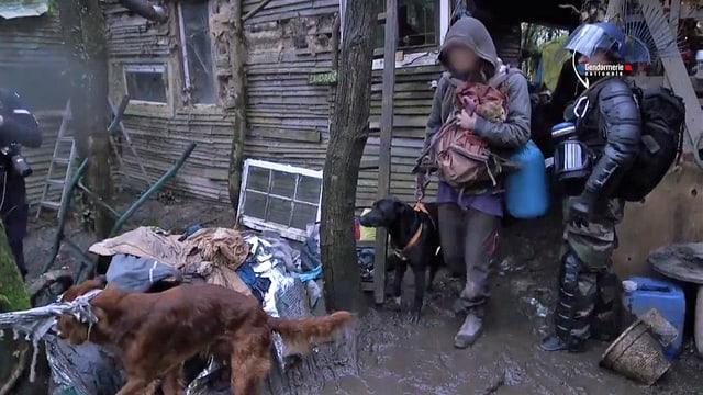 Ein Besetzer mit Hund und Katze verlässt seine Hütte.