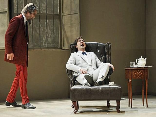 Ein alter Mann steht neben einem Stuhl auf dem ein junger Mann sitzt der lacht.